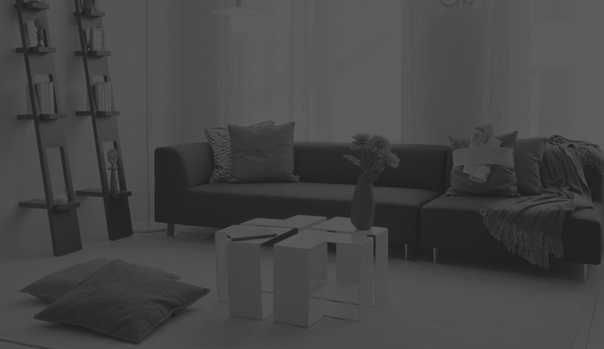 zwart wit foto van sofa met tafeltje en boeken rek